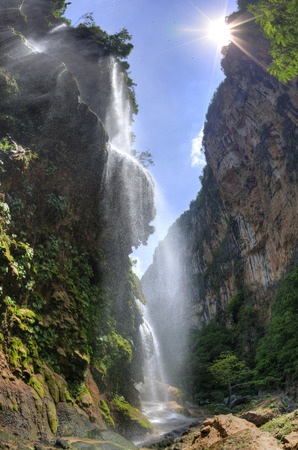 HDR image of beautiful El Aguacero waterfall in Chiapas, Mexico pouring into deep canyon with sun shining above