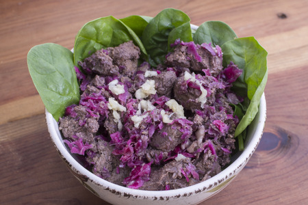 Closeup bowl of freshly cooked beef liver with red sauerkraut, garlic and raw spinach leaves on rustic wood table