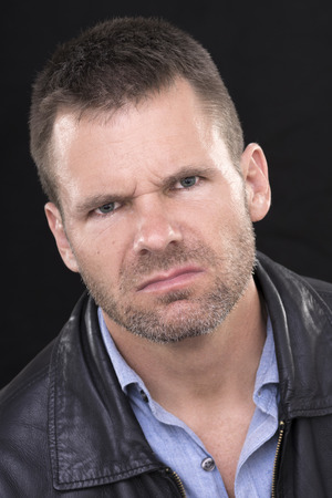 irked: Closeup portrait of angry disgruntled Caucasian man with short hair and stubble with mean expression on black background