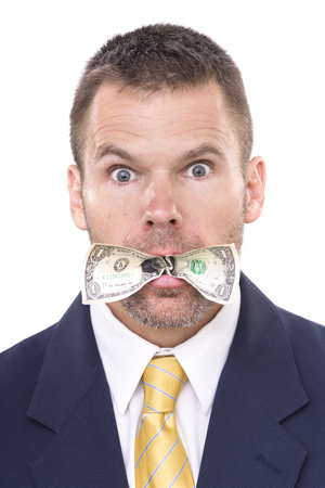 eyes wide open: Closeup portrait of handsome Caucasian businessman eating dollar bill stuffed in his mouth with surprised eyes wide open on white background