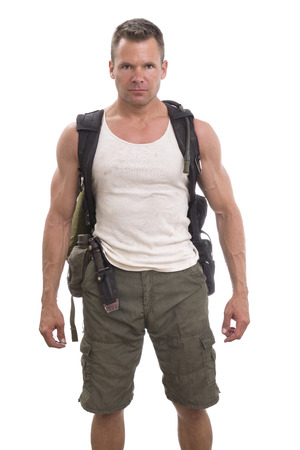 Handsome muscular man with hiking and expedition gear wearing cargo shorts and tank top standing on white background with bold action figure expression Imagens
