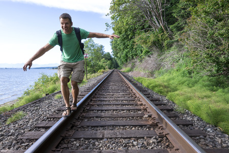 Fun-loving handsome Caucasian man shows his free spirit as he balances on railroad tracks while hiking along beautiful Canadian coast in Surrey, British Colombia