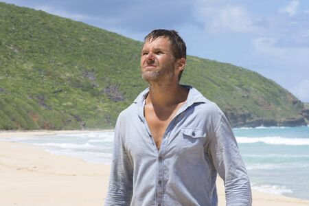 castaway: Rugged filthy Caucasian castaway man with beard and dirty shirt lost on deserted island beach under bright sun Stock Photo