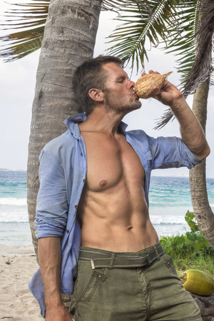 pectoral: Muscular rugged Caucasian man with sexy torso wearing unbuttoned shirt drinks water from fresh coconut under palm tree on Caribbean island beach Stock Photo
