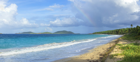 water  panoramic: Colorful rainbow in clouds over Culebrita island in panoramic Zoni Beach scene with turquoise blue Caribbean water of Isla Culebra in Puerto Rico