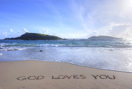 Message in sand reads God Loves You on tropical Caribbean beach of Isla Culebra in Puerto Rico with small islands in background Stock Photo