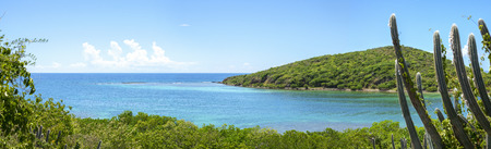 Beautiful wide panoramic of Melena Bay and Soldier Point with blue and turquoise sea bordered by dense green vegetation on Caribbean island of Isla Culebra in Puerto Rico Stock Photo