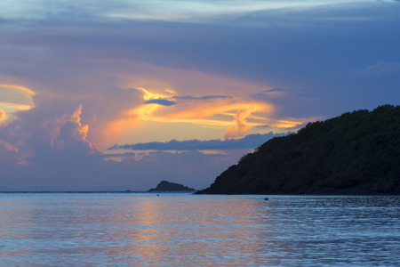 vividly: Vividly illuminated opening in gray clouds during sunset over the sea on the Caribbean island of Isla Culebra in Puerto Rico