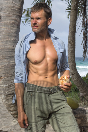 button down shirt: Handsome scruffy Caucasian man with fit muscular torso wearing open button down shirt holding coconut under palm tree on tropical island beach