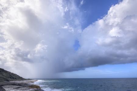 Rain falls from dark clouds out at sea from rocky northeast coast of Isla Culebra in Caribbean Sea
