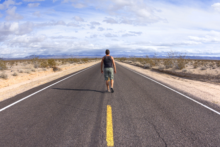 Man walking away from camera down center yellow line of black asphalt highway in barren Mojave Desert in California on sunny day with scattered clouds