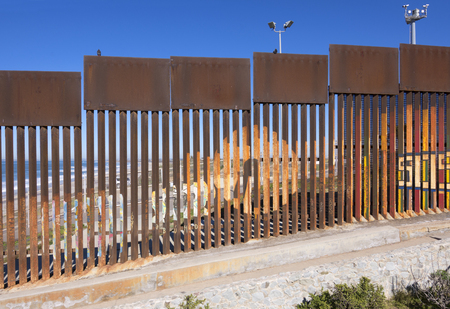 Steel fence made of vertical girders separating Mexico from the United States in a secured political boundary in Playas de Tijuana in Mexico