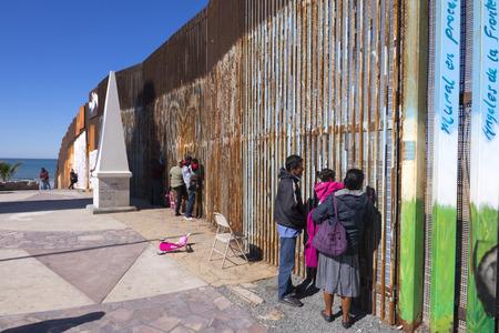 PLAYAS DE TIJUANA, MESSICO - 28 GENNAIO 2017: Le famiglie messicane che vivono a Tijuana visitano con i membri della famiglia che vivono negli Stati Uniti incontrando il muro di confine di Playas de Tijuana in un sabato mattina d'inverno soleggiato. Editoriali