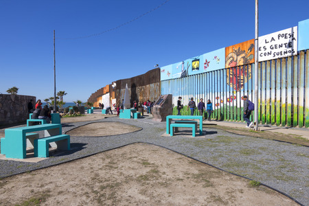 homeland: PLAYAS DE TIJUANA, MEXICO - JANUARY 28, 2017: The wall seperating Mexico and the United States is a richly decorated mural stirring deep emotions regarding the controversy surrounding homeland security and the Trump administration. Editorial