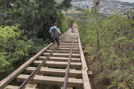 KOKO CRATER, OAHU, USA - JANUARY 20, 2017: Hikers carefully maneuver down the old cart rail leading down from the summit of Koko Crater, a popular day hike destination near Honolulu.