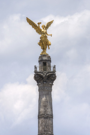 angel de la independencia: Gold-plated sculpture representing the Angel of Independence at top of victory column on Mexico Citys famous Paseo de la Reforma on cloudy day