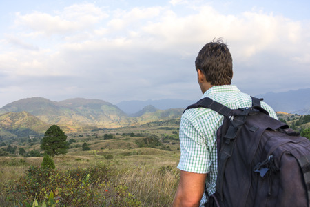 Male Caucasian hiker with black backpack stands overlooking scenic hilly landscape in late afternoon light on trail to El Chichonal volcano in Mexico
