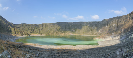 Panoramic interior of El Chichonal volcano with green sulfuric lake in crater and active fumaroles on sunny day in Chiapas, Mexico