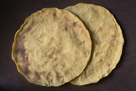 yellow corn: High angle closeup two handmade yellow corn tortillas on wooden table in Mexico