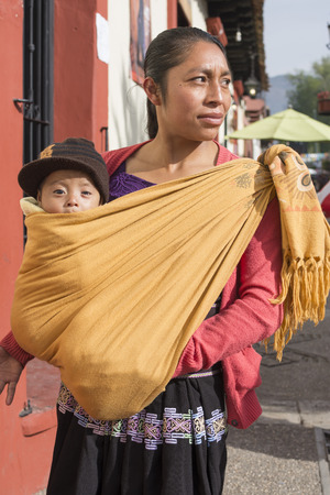 SAN CRISTOBAL DE LAS CASAS, CHIAPAS, MEXICO - FEBRUARY 20, 2017: A Tsotsil woman carries her six-month-old baby in a traditional cotton shawl on a Monday morning as she begins her daily activities.