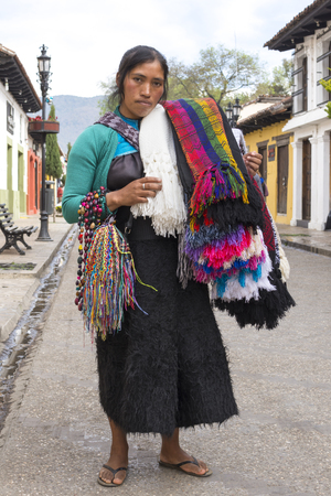 SAN CRISTOBAL DE LAS CASAS, CHIAPAS, MEXICO - FEBRUARY 20, 2017: A Tsotsil woman wearing traditional wool skirt carries an assortment of colorful shawls, bracelets and necklaces to sell to tourists visiting this culturally-rich city.