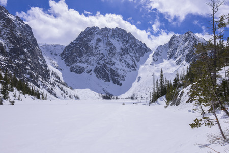 Rocky snow covered Dragontail Peak rises above frozen Colchuck Lake under bright sunshine in northern Cascade Mountains near Wenatchee, Washington in April 2017