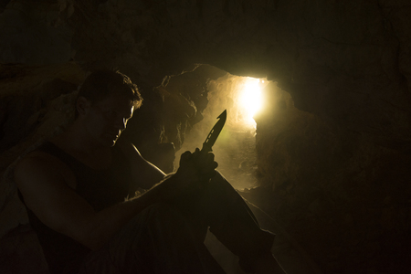 holding a knife: Silhouette with rim light of adventure man sitting in dusty cave looking at and holding survival knife Stock Photo