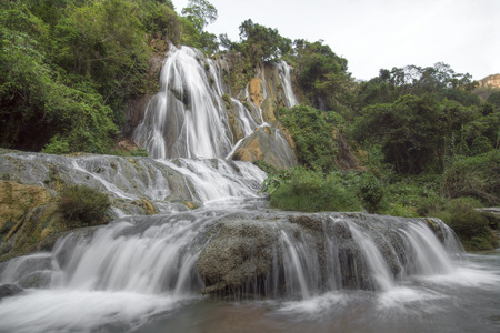 cloudy day: Beautiful cascading water of La Conchuda waterfall in Rio la Venta Canyon in Chiapas, Mexico surrounded by lush green vegetation on cloudy day