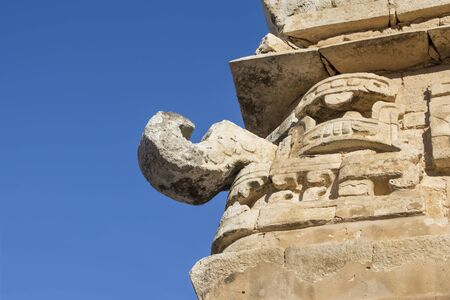 Closeup low angle stone sculpture of rain god Chaac on corner of temple building at Chichen Itza on clear sunny day in Yucatan, Mexico