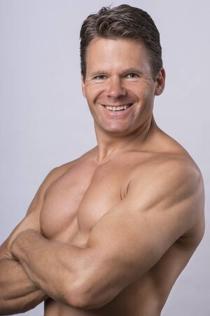Handsome Caucasian middle-aged man in his forties smiling and posing with shirt off on light gray background photo