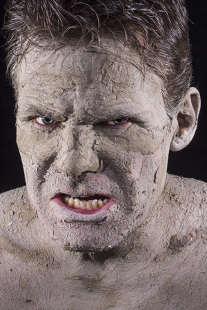 Closeup portrait of hideous looking man covered in dry flaky mud resembling a mummified corpse on black background photo