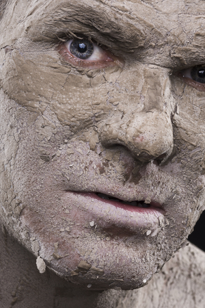 Macro closeup scary face of man with dry flakes of cracked mud covering his skin like a mummified corpse photo