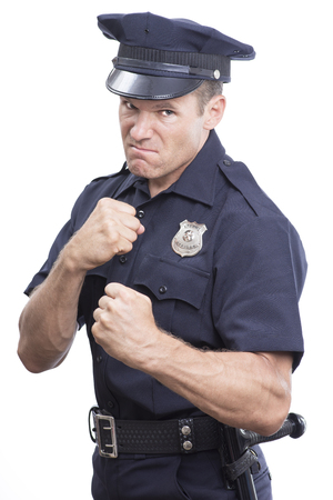 Aggressive uniformed Caucasian police officer ready to fist fight on white background