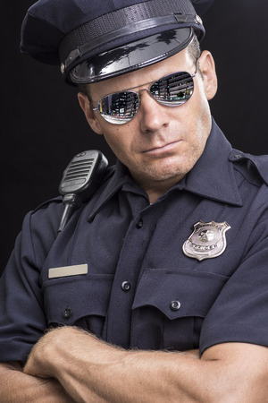 Portrait of tough and serious Caucasian police officer wearing reflective sunglasses and crossing arms on black background photo