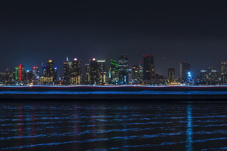 Wide angle San Diego skyline over bay with trailing boat lights and reflections over water from long exposure