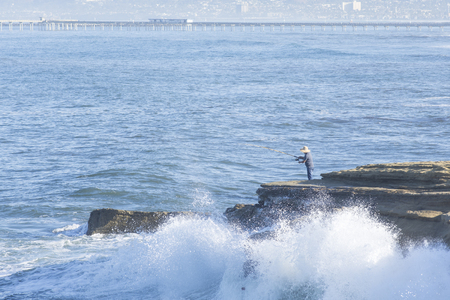 Waves crash against the rocky cliffs of Ocean Beach, California as a surf fisherman fishes from above the splash zone on a summer morning