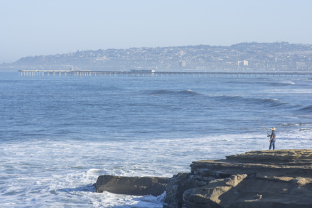 Beautiful coastline of Ocean Beach in San Diego, California with pier and man surf fishing from rocky shore on summer morning Stock Photo
