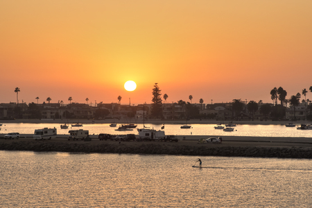 Vivid orange sky during warm summer sunset over Mission Beach and Mission Bay with campers, boats and paddle boarder on the water