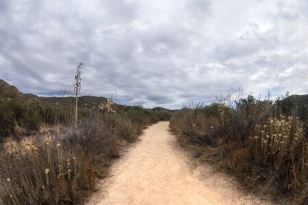 Moody sky with gray storm clouds over dry arid southern California landscape parted by dirt trail