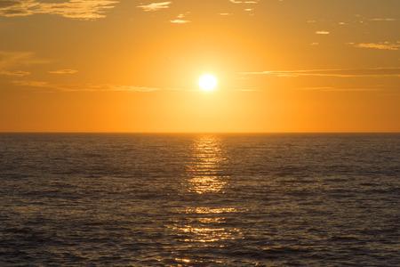 Levendige gouden zonsondergang gecentreerd over open oceaanhorizon met kalm oppervlak