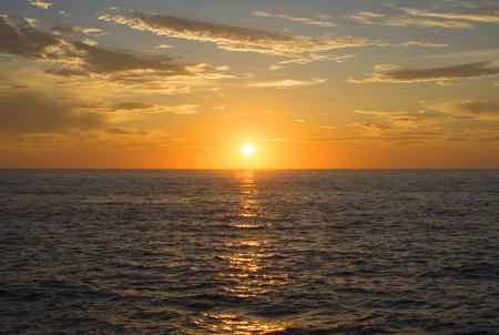 Mooie brede hoek gouden zon gecentreerd over veranderlijke oceaanhorizon