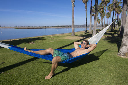 Muscular sexy Caucasian man with fit body wearing board shorts and sunglasses relaxes in Mexican hammock while tanning in park by Mission Bay in San Diego, California Stockfoto
