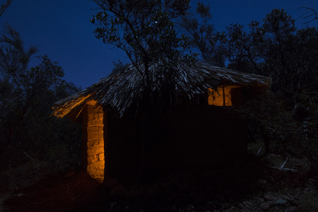 Primitive adobe hut with thatched roof illuminated at night by moonlight and interior campfire lights up interior