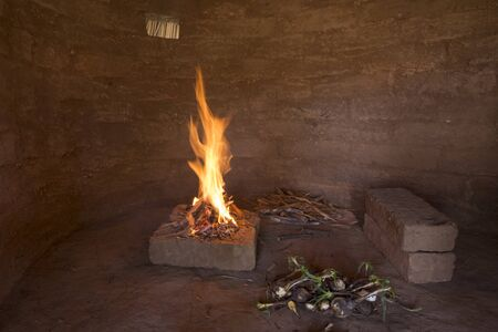 Small campfire burning on bricks inside primitive adobe hut with dirt floor and wild soap plant roots to be roasted