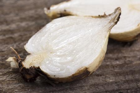 Macro closeup sliced Chlorogalum parviflorum soap plant bulb root on wood table