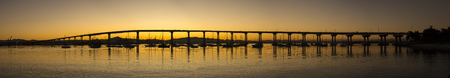 Scenic panorama silhouette of San Diego - Coronado Bay Bridge with clear orange sky at sunrise and reflections of boats on surface of water