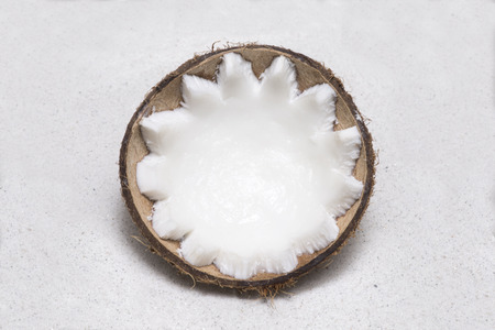 Half coconut in shell with toothed cut meat lying on fine white beach sand
