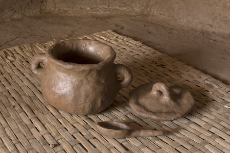 Primitive fresh thrown pottery consisting of bowl, lid and spoon sit drying on woven mat inside adobe hut with earthen floor Standard-Bild
