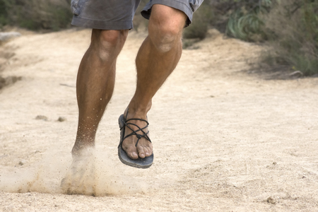 Telephoto shot legs of rugged male runner in shorts and primitive sandals running hard on dirt trail Stockfoto