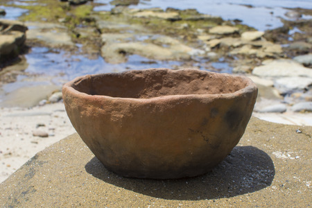 Primitive handmade pottery bowl on rock at beach on sunny day
